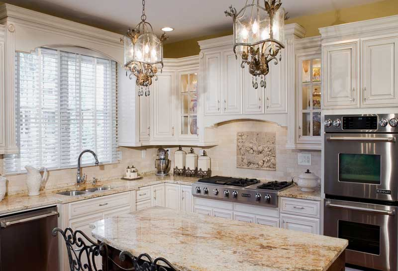 Kitchen with white cabinets, marble counter tops and stainless steel appliances.