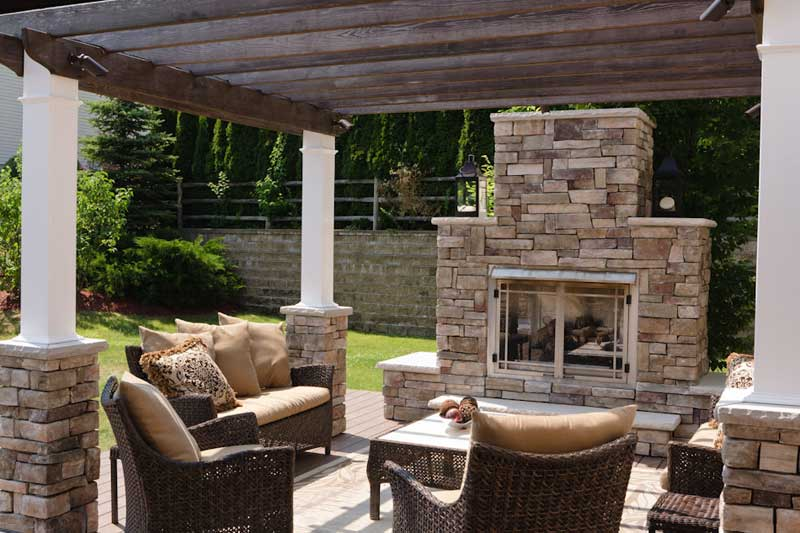 Stone work outdoor fireplace with patio furniture and overhead awning.