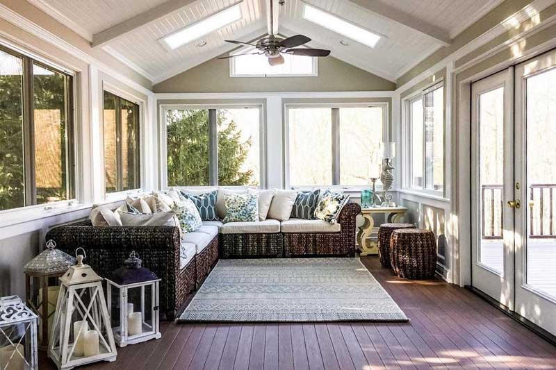 Sunroom with large windows, skylights in high ceiling and wooden floor.