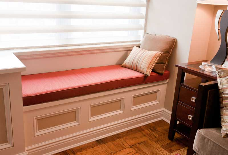 Built-in window seat with red cushins and vertical window blinds.