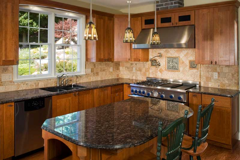 Dark wood kitchen cabinets, granite counter tops and stainless steel appliances.
