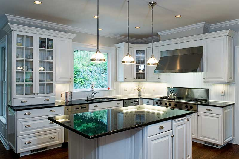 White kitchen cabinets and walls and center island with black counter tops.
