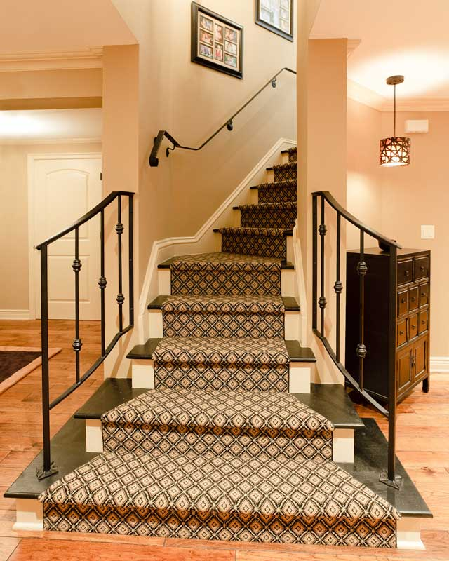 Carpeted stairs with iron rails leading upstairs.