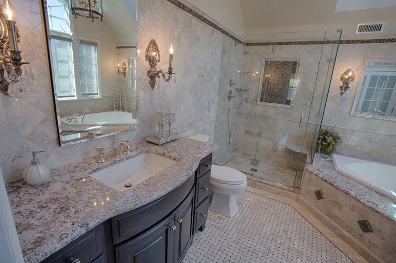 All marble bathroom, stand-up shower with glass door and tub angled into corner.