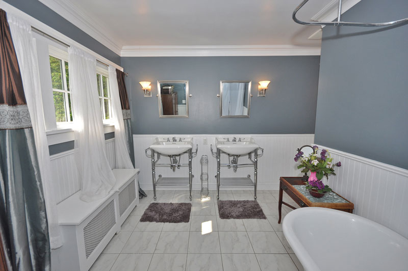 Bathroom with marble floors, two sinks with chrome legs and free standing tub in corner.