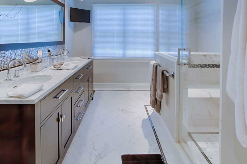 Marble bathroom with two sink vanity on left and walk-in shower on right.