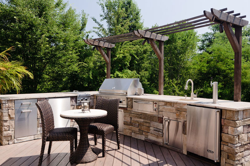 Outdoor patio with BBQ grill, sink and refrigerator.