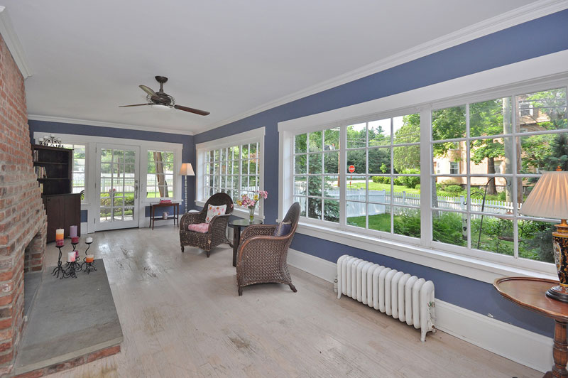 Sun room with brick fireplace and large windows looking into outdoor garden.