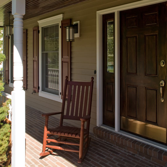 Outdoor patio of home with siding, windows and front door.