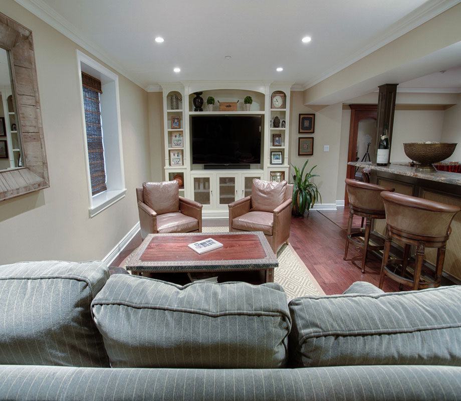 Finished Basement With Large Screen TV and Bar on the Right