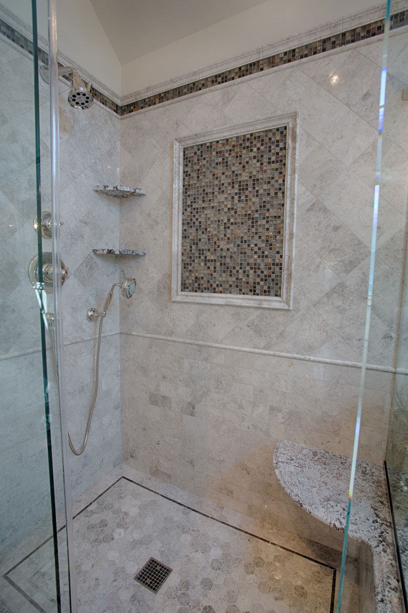 Stand up shower with marble tile floors and walls