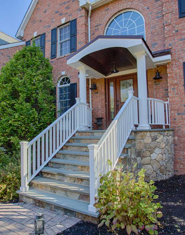 White railings on both side of stone stairs leading up to front entrance with wood door. Palladium windows are on both sides.