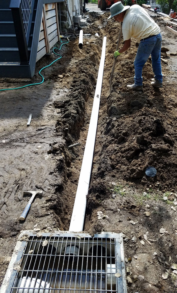 Man digging drainage ditch with PVC pipe and junction box.
