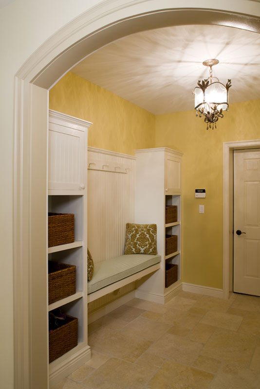 Mud Room With Yellow Walls, Curved Archway, Tile Floor and Builtin Seat