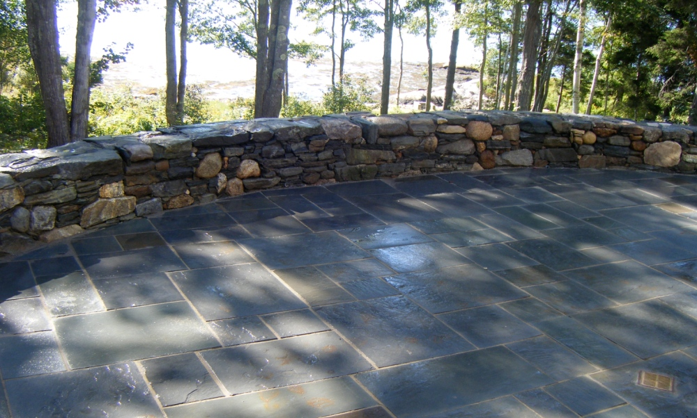 Flagstone exterior walkway with circular rock wall as a border.