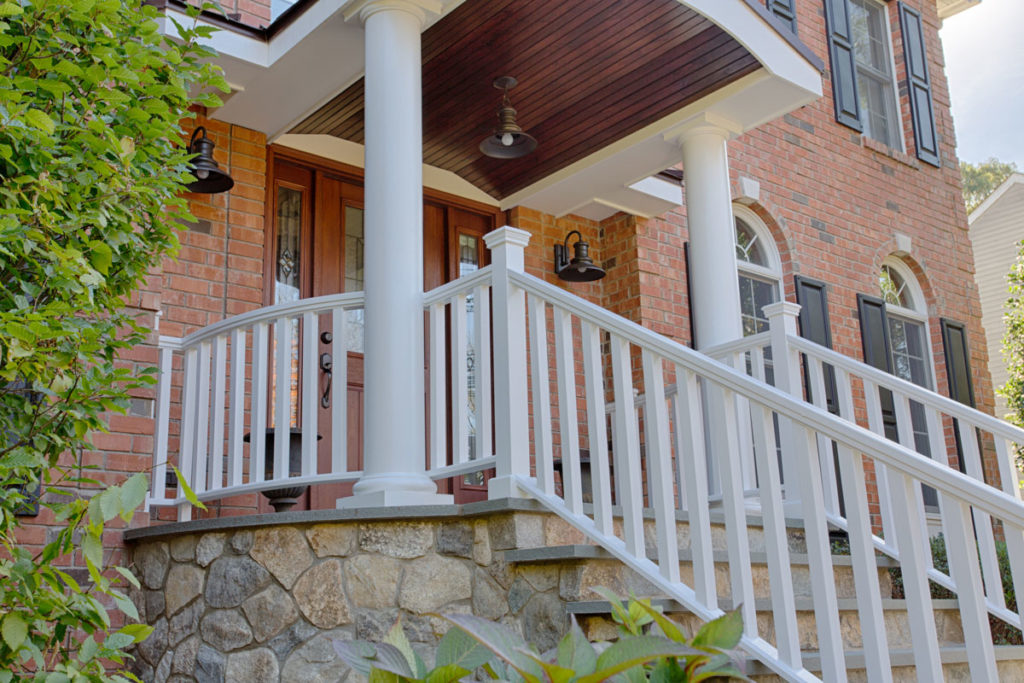 White support columns on stoop and white railings down the stairs