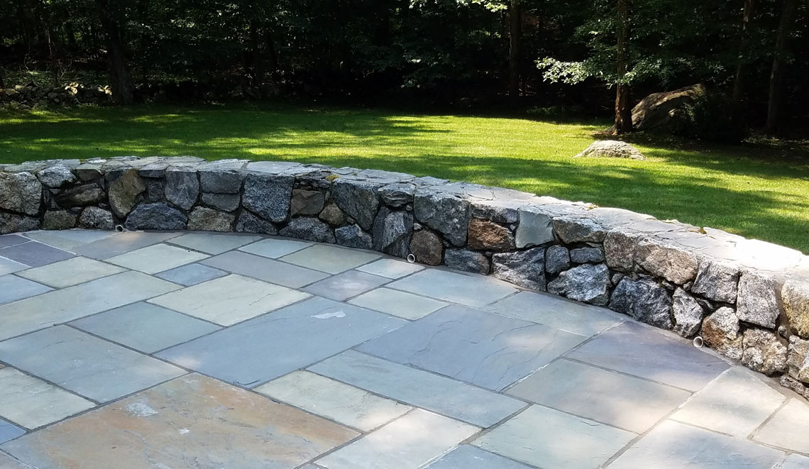 Stone wall two feet high with green lawn in background and bluestone patio in front.